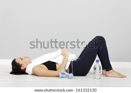 Young woman lying down after long fitness workout. - stock photo