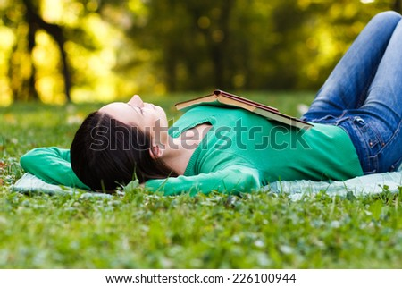 Young woman lying down in nature and sleeping,Resting in nature - stock photo