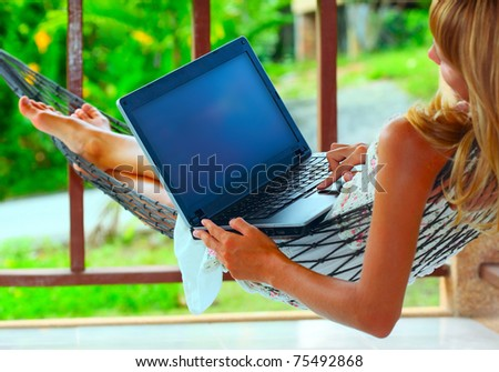 Young woman lying in a hammock and looking to a laptop - stock photo