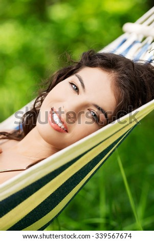 Young woman lying in a hammock in garden - stock photo