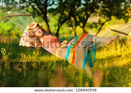Young woman lying in a hammock in garden and reading a book and eating peach