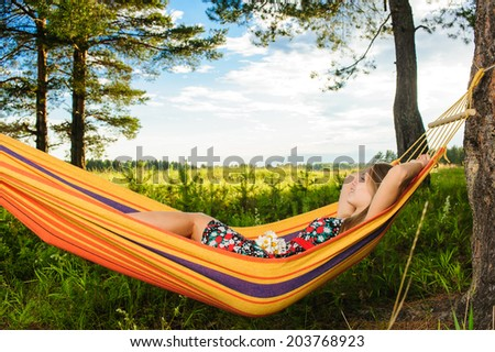 Young woman lying in a hammock in garden with a bouquet of flowers of camomile