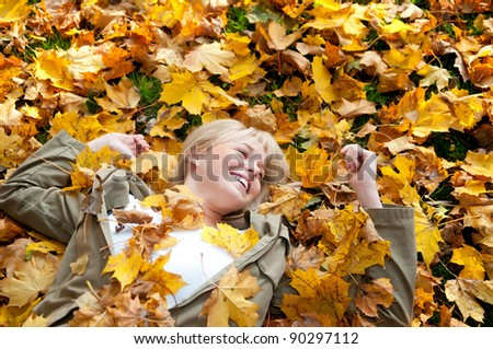 young woman  lying in autumn leaves - stock photo