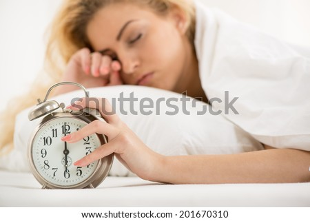 Young woman lying in bed in the morning. She is waking up with alarm clock. - stock photo