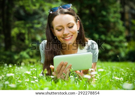 Young woman lying in grass and using digital tablet