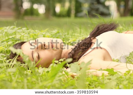 young woman lying in grass, toned image