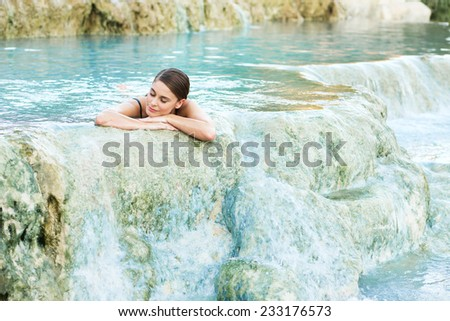 Young woman lying in the natural pool, Saturnia, Italy