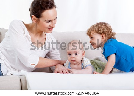 Young woman lying on a couch with two kids
