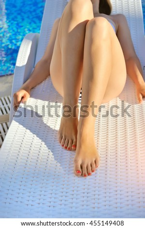 Young woman lying on a lounger near the swimming pool. Sunbathing woman - stock photo