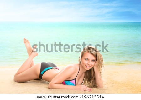 Young woman lying on beach at tropical sea