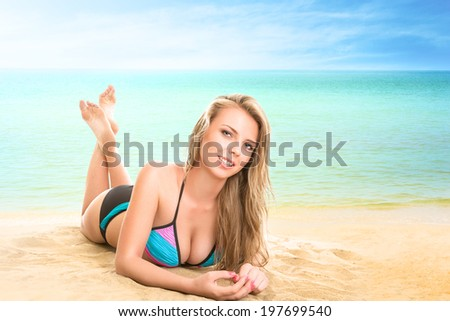 Young woman lying on beach at tropical sea - stock photo