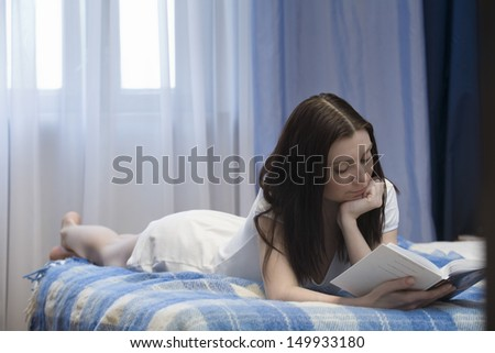 Young woman lying on bed and reading book at home - stock photo