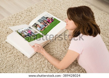 Young Woman Lying On Carpet Looking At Family Photo Album - stock photo