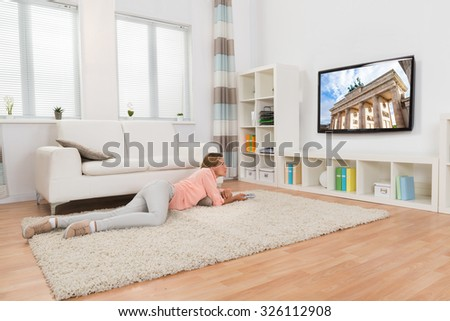 Young Woman Lying On Carpet While Watching Television At Home - stock photo