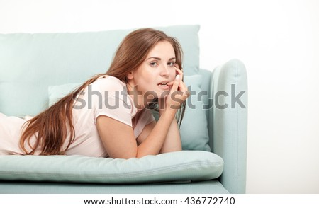 Young woman lying on couch at home looking to camera, domestic style shoot - stock photo