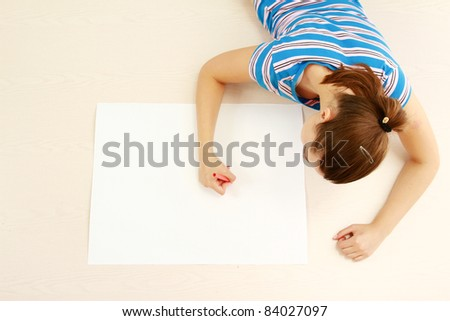 Young woman lying on floor and drawing isolated over white. Top view