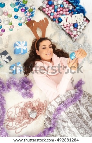 Young woman lying on floor, christmas ornament all around, smiling happy, having fun.