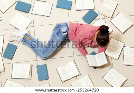 Young woman lying on floor with books and reading, top view. Blurred text is unreadable - stock photo