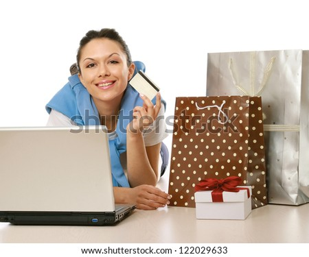 Young woman lying on floor with laptop and holding credit card isolated on white background