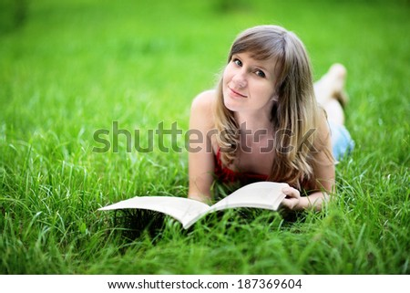 Young woman lying on grass and reading book