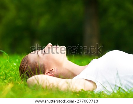 Young woman lying on grass and relaxing in park. - stock photo