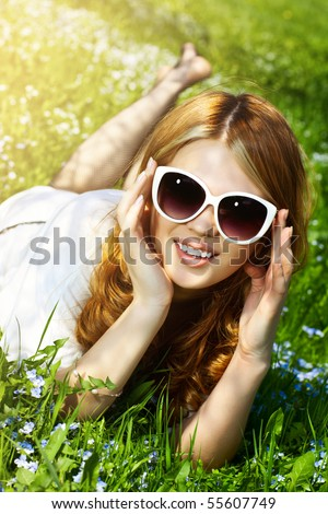 Young woman lying on grass fashion portrait. - stock photo