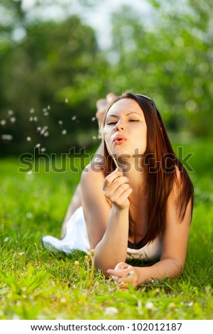 Young woman lying on grass in park and wishing on a dandelion