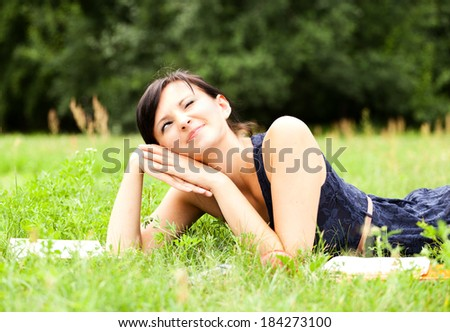 Young woman lying on grass with book, smiling - stock photo