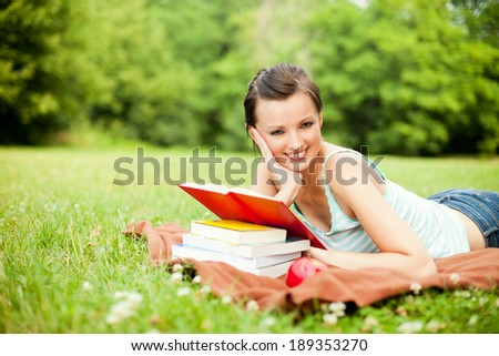 Young woman lying on grass with book, smiling