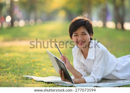 young woman lying on green grass park with pencil and note book in hand thinking something ,project,dream,hope,solution in future - stock photo