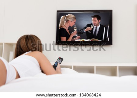 Young Woman Lying On Her Bed And Watching Television - stock photo