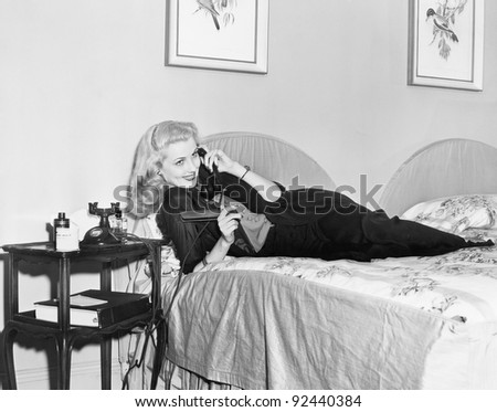 Young woman lying on her bed in the bedroom and talking on the telephone - stock photo
