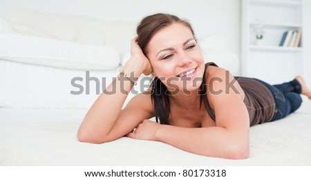 Young woman lying on her belly in her living room