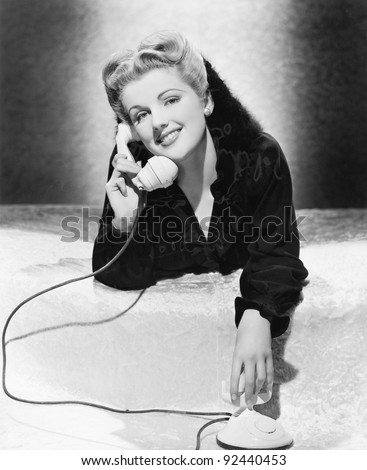 Young woman lying on her stomach and talking on the telephone - stock photo