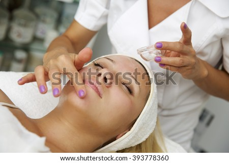 Young woman lying on massage table receiving face massage. Beauty treatment concept. - stock photo