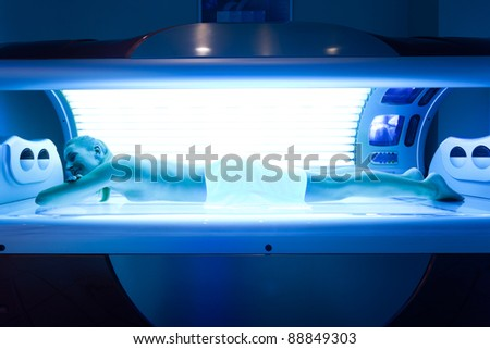 Young woman lying on tanning bed for a beautiful complexion - stock photo