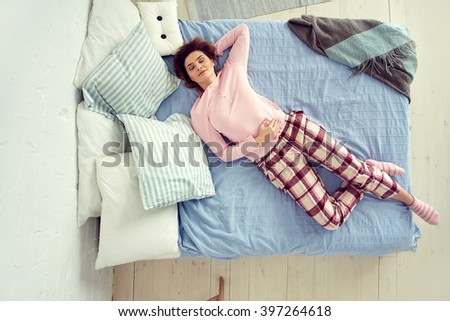 young woman lying on the bed. girl relaxing at home - stock photo