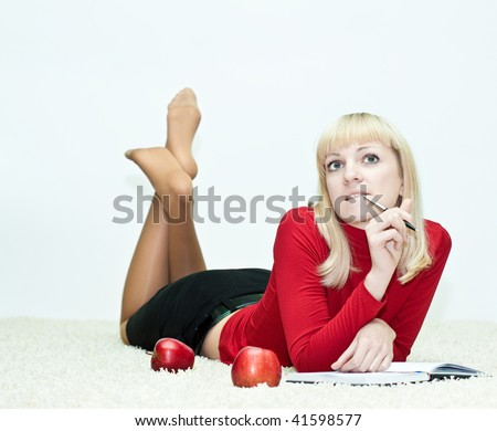 Young woman lying on the floor and writing in a diary