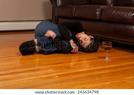 Young woman lying on the floor passed out in the fetal position with a wine glass - stock photo