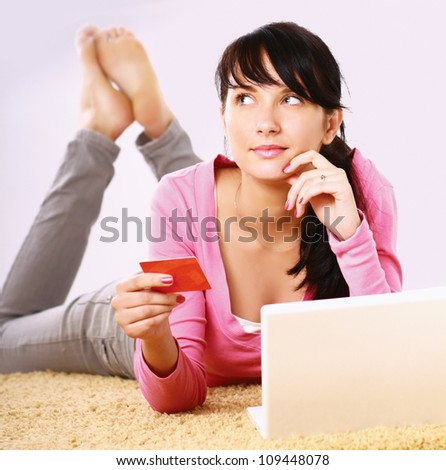 Young woman lying on the floor  with credit card - stock photo