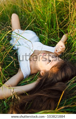 young woman lying on the grass and dreaming - stock photo