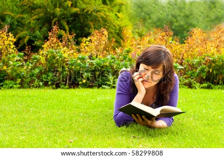 young woman lying on the grass and reading a book  in a park - stock photo