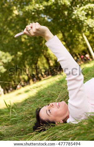 young woman lying on the grass taking a selfie