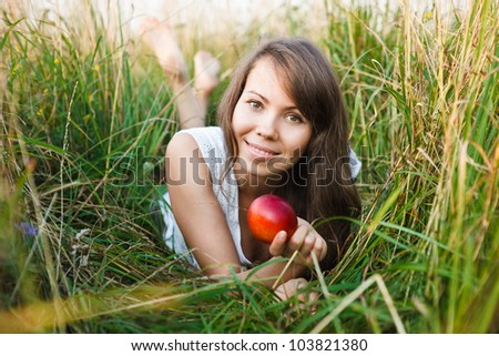 young woman lying on the grass with apple - stock photo