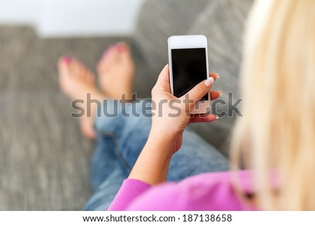 Young woman lying on the sofa and holds mobile phone - stock photo