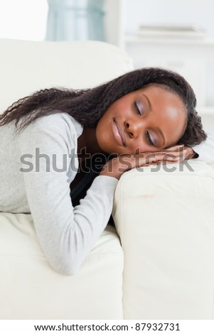 Young woman lying on the sofa with eyes closed