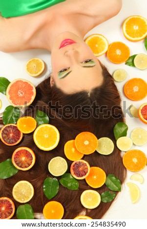 young woman lying on white background with oranges around her hair - stock photo
