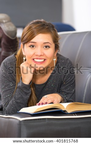 Young woman lying stomach down on dark sofa, supporting head using hands, reading and smiling into camera - stock photo
