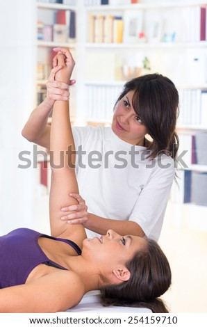 young woman lying while getting a massage from specialist concept of physiotherapy - stock photo