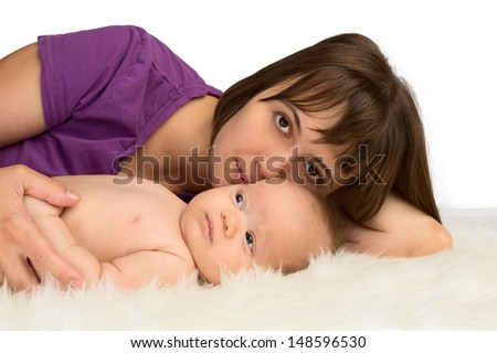 Young woman lying with her baby daughter on a sheepskin, isolated